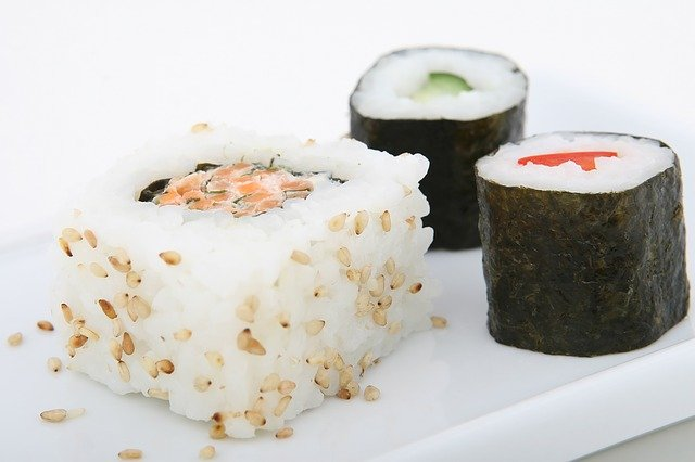 A piece of cake sitting on top of sushi on a plate